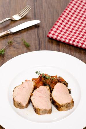 vertical format: Roasted pork fillet with tomatoes and olives in vertical format