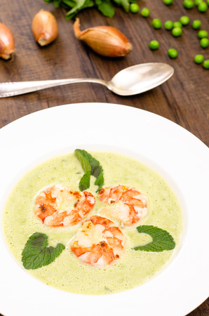 vertical format: Pea cream soup with shrimps and mint in vertical format