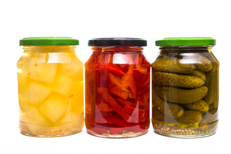 Mustard, paprika and gherkin pickles in a glass white isolated
