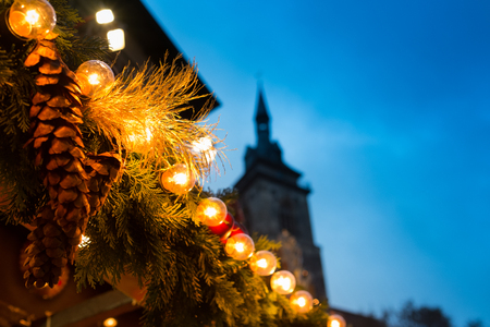 Lights and fir branches as christmas decoration with steeple in the sky