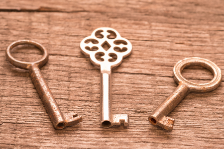 tooled: Old keys with rust and patina on wooden board
