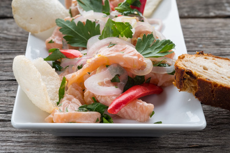 an onions: Snack ceviche with salmon, onions chili and krupuk