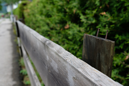 Gray wooden fence with rusty nails and blurred background