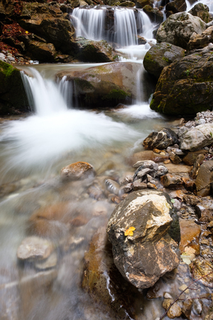 Waterfall of mountain stream Faltenbach with rocks and yellow leaf in Germany Stock Photo
