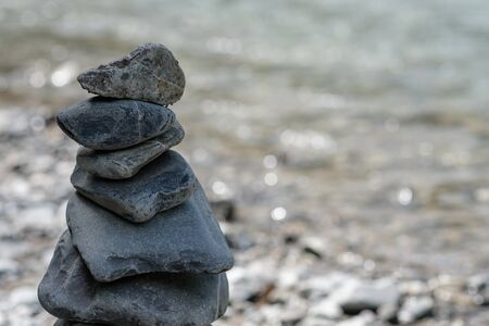 Stone on stone as cairn in balance with the river in background