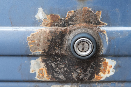 Rotting car lock with rust and blue varnish as close up Stock Photo