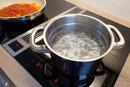 Boiling water in a cooking pot an a pan on a induction stove Stok Fotoğraf