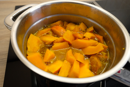 Orange Hokkaido pumpkin in a cooking pot with steam
