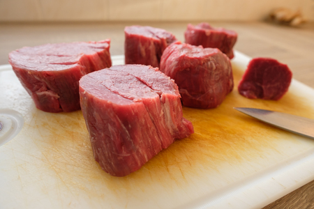 Raw beef fillet in pieces on a cutting board with kitchen knife