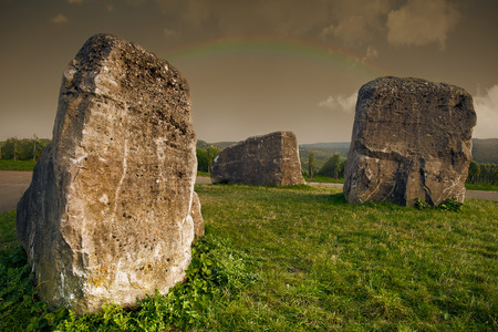 Mystic landscape with rocks on a meadow and rainbow in the sky