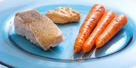 Zander fish filet roasted with carrots and hummus on blue plate