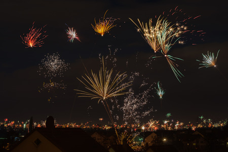 Farbiges Feuerwerk am dunklen Himmel zu Neujahr über einem Dorf Standard-Bild