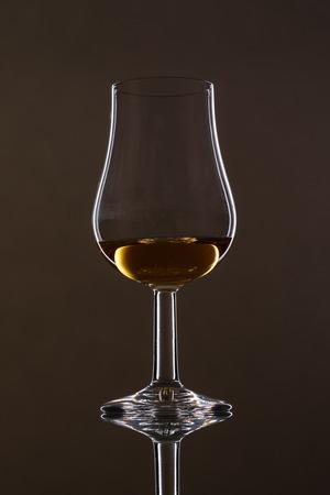 Glass with scottisch Whisky und reflection with black background 写真素材