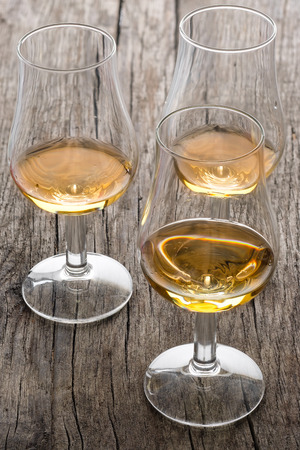 Glasses with scottish single malt whisky on wood in vertical format