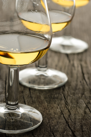 Glass with single malt whisky on wooden board in vertical format Imagens - 123217611