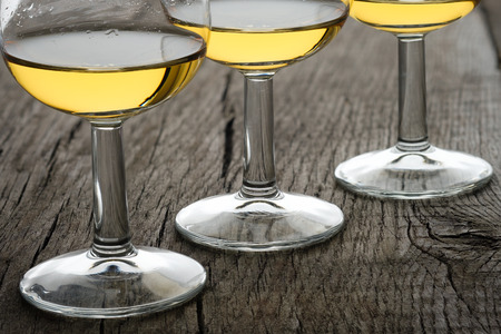 Close-up glasses with single malt whisky in back lit on rustic wooden board