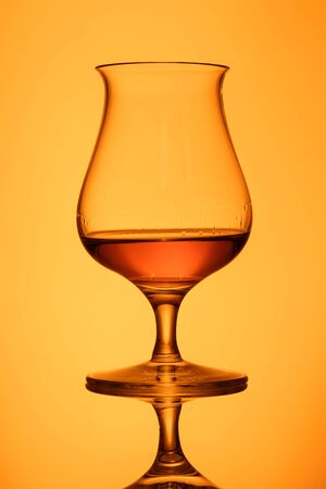 Glass with orange whisky in back lit with reflection