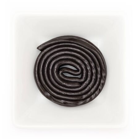 Black licorice wheel in a white bowl in top view