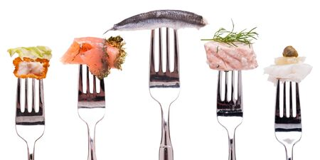 Different kind of fish on a fork white isolated