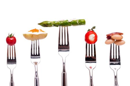 Different vegetables on a fork white isolatede