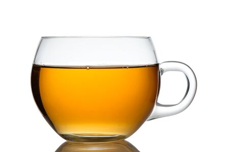 Tasse en verre de thé noir orange en gros plan rétroéclairé