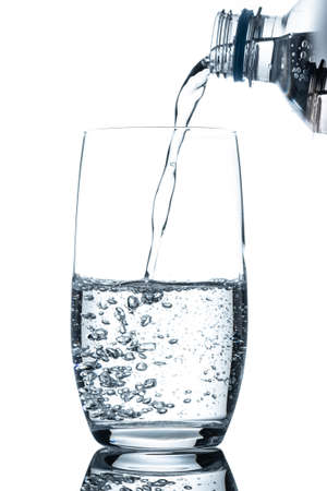 Bottle mineral water pouring in glass in vertical format 写真素材