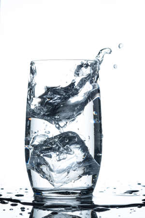 Water glass ice cube splash in vertical format and back lit Imagens