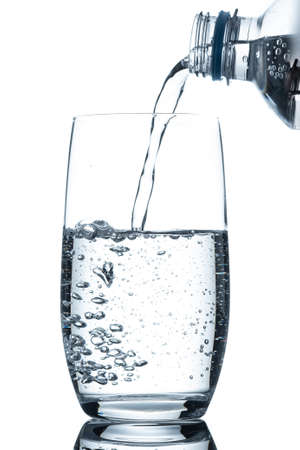 Glass with mineral water pouing in with air bubbles in back lit