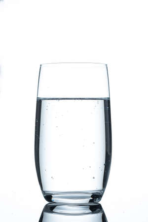 Glass of mineral water in back lit and vertical format 写真素材