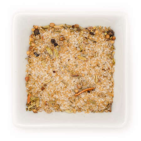 Dry beige herb mixture for fish in bowl top view