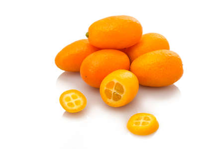 Kumquat fruit on heap with slices white isolated