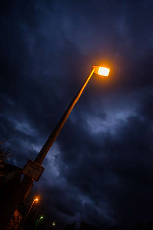 ellow light of a street lamp with clouds in the sky wide-angle