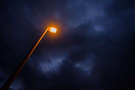 Yellow light of street lamp with cloudy sky in dawn Stok Fotoğraf