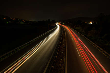 Car light trails on a highway in morning night