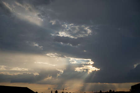 Dark sky with clouds and sunbeams of the sun cloudscape