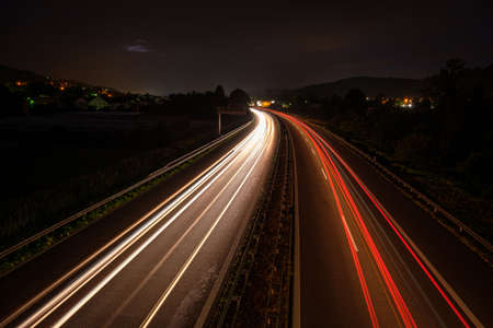 Overhaul with red car light trails on a motorway in night dawn