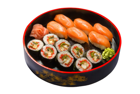 Set of sushi and nigiri with salmon and eel in a round wooden black plate photo