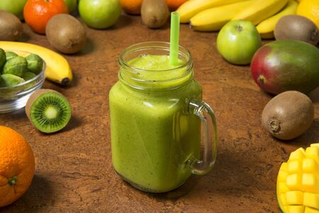 Green smoothie banana kiwi mango orange and apple in glass jar with fresh ingredients on a brown table. Selected focus. Archivio Fotografico
