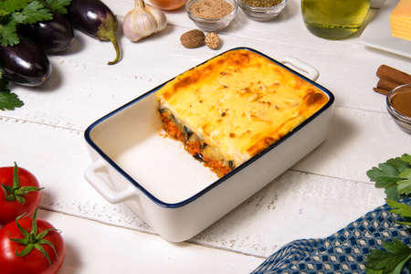 Greek Moussaka close up in casserole dish with the ingredients on the white rustic table. 免版税图像