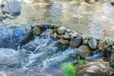 mountain river waterfall between stones in summer time