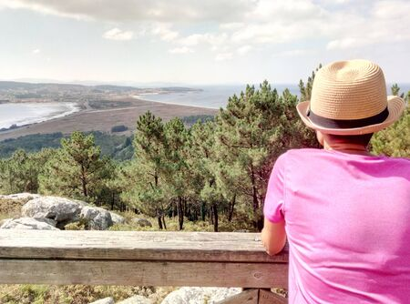 Young hiker woman contemplating landscape to the sea from mountain viewpoint
