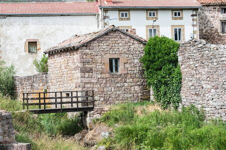 mountain village of Spain with stone houses and bridge over the river in summer