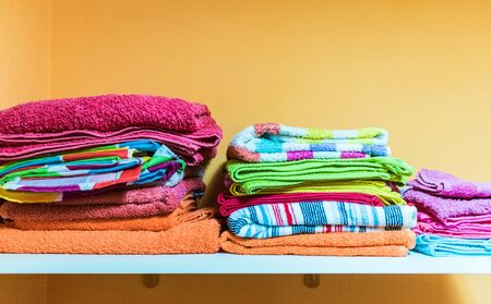 white wooden band on orange wall with many colored towels 스톡 콘텐츠