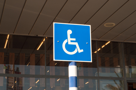 disabled parking sign: blue and white sign of disabled parking on the street