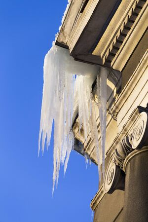 Large icicles hang from a house roof. Dangerous large icicles.