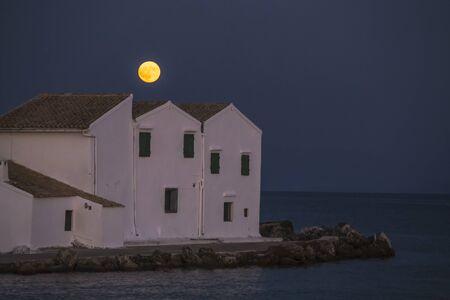 Full moon over the church of Panagia Vlacherna. Cape Kanoni, Corfu, Kerkyra, Greece.