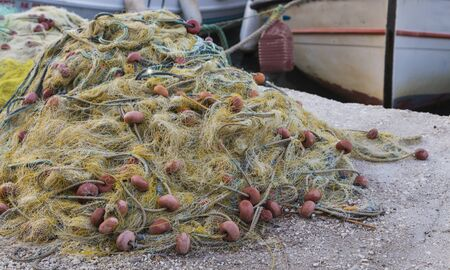 Traditional fishing net with floats on the shore after fishing on the background of boats.