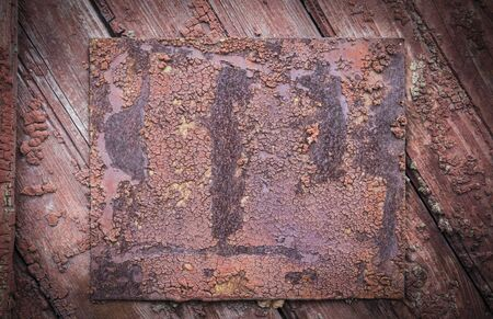 Old vintage rusty metal plate on wooden board