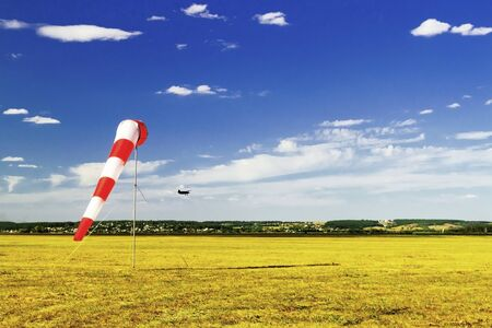 red and white windsock wind sock on blue sky, yellow field and clouds background, silhouette of vintage airplane in the sky