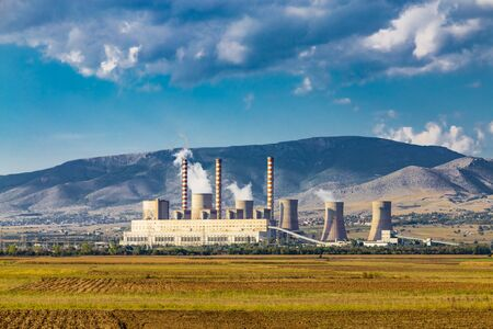 Steaming coal power plant over yellow agriculture field on the mountains background. ?nvironmental pollution concept.